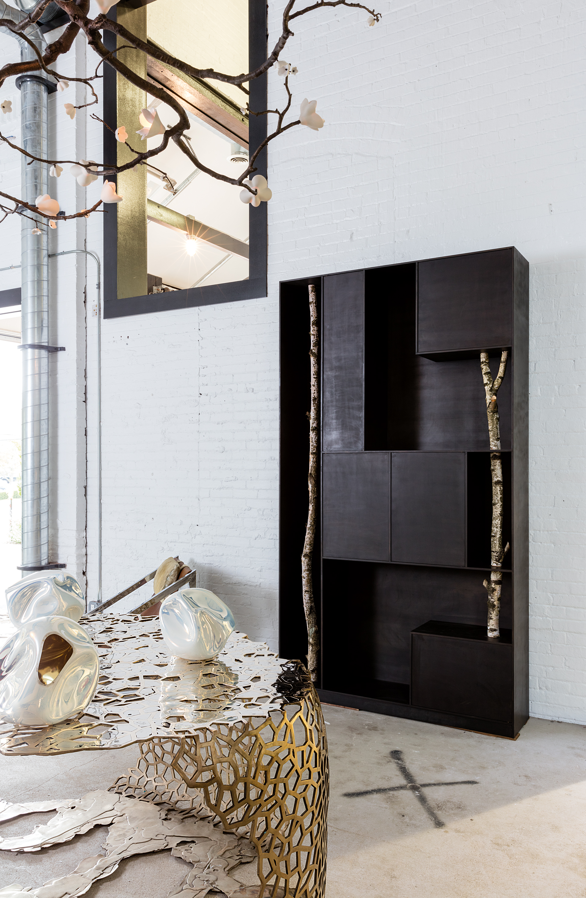 A cabinet by the Italian architect Andrea Branzi is next to a 2015 lace-like bronze table by the American designer David Wiseman.