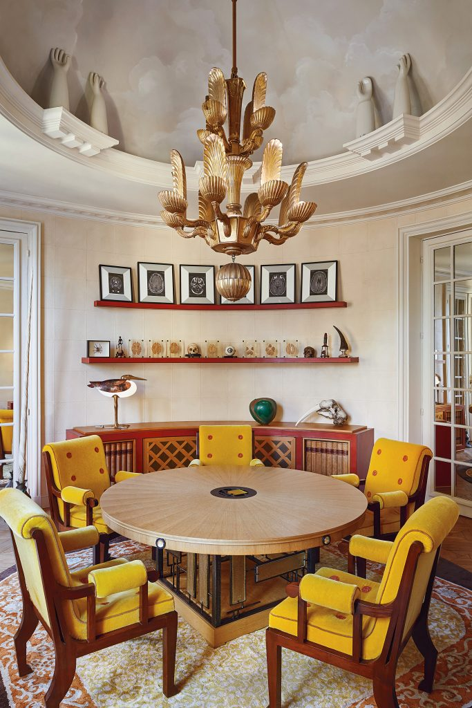 The 1930s chandelier in the dining room is layered with gilded, carved-wood  shells. The 1940s Mexican dining chairs surround a contemporary table of  wood, ...