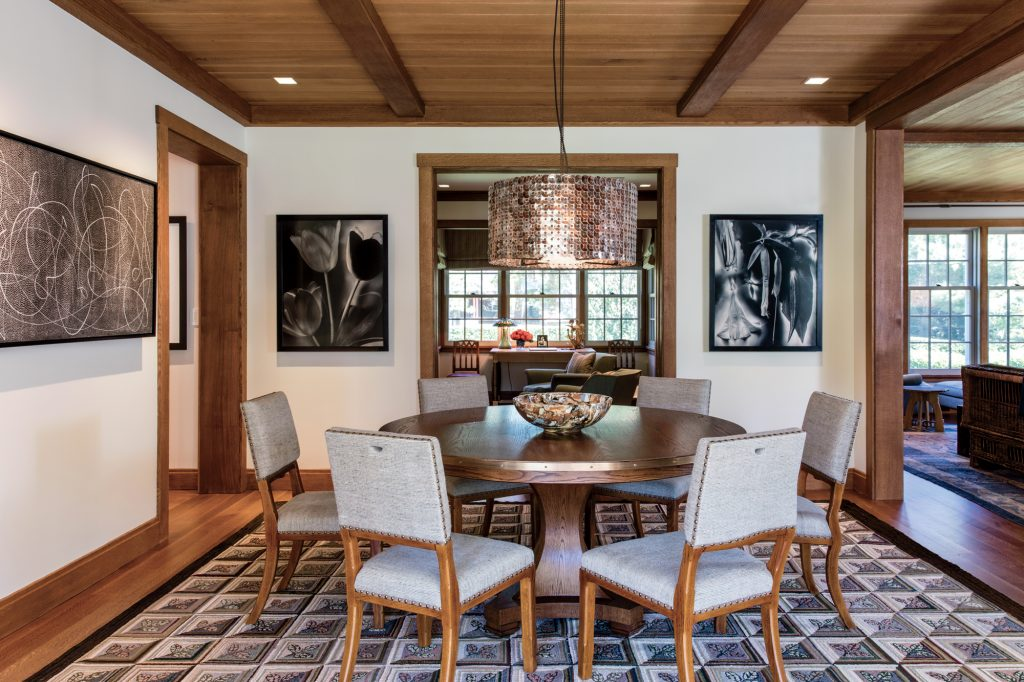 The open dining area has been situated between the kitchen and the living room. American artist Elliott Puckette's 2010 Lacerta hangs on the wall on the left. The hanging fixture is from the McEwen Lighting Studio, in Berkeley, California.