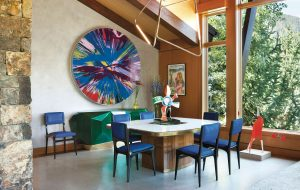A Damien Hirst Spin painting makes a splashy statement in the dining area of Sue Hostetler's Aspen home designed by Sara Story.