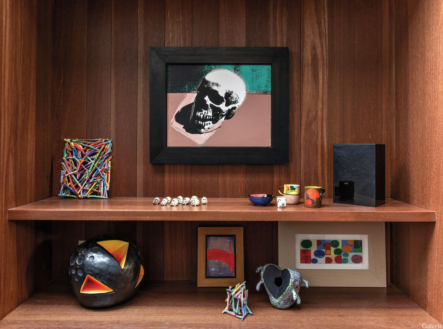 An Andy Warhol skull is grouped with works by Arnoldi, Ken Price, John McCracken, and Natalie Arnoldi in a bookcase.
