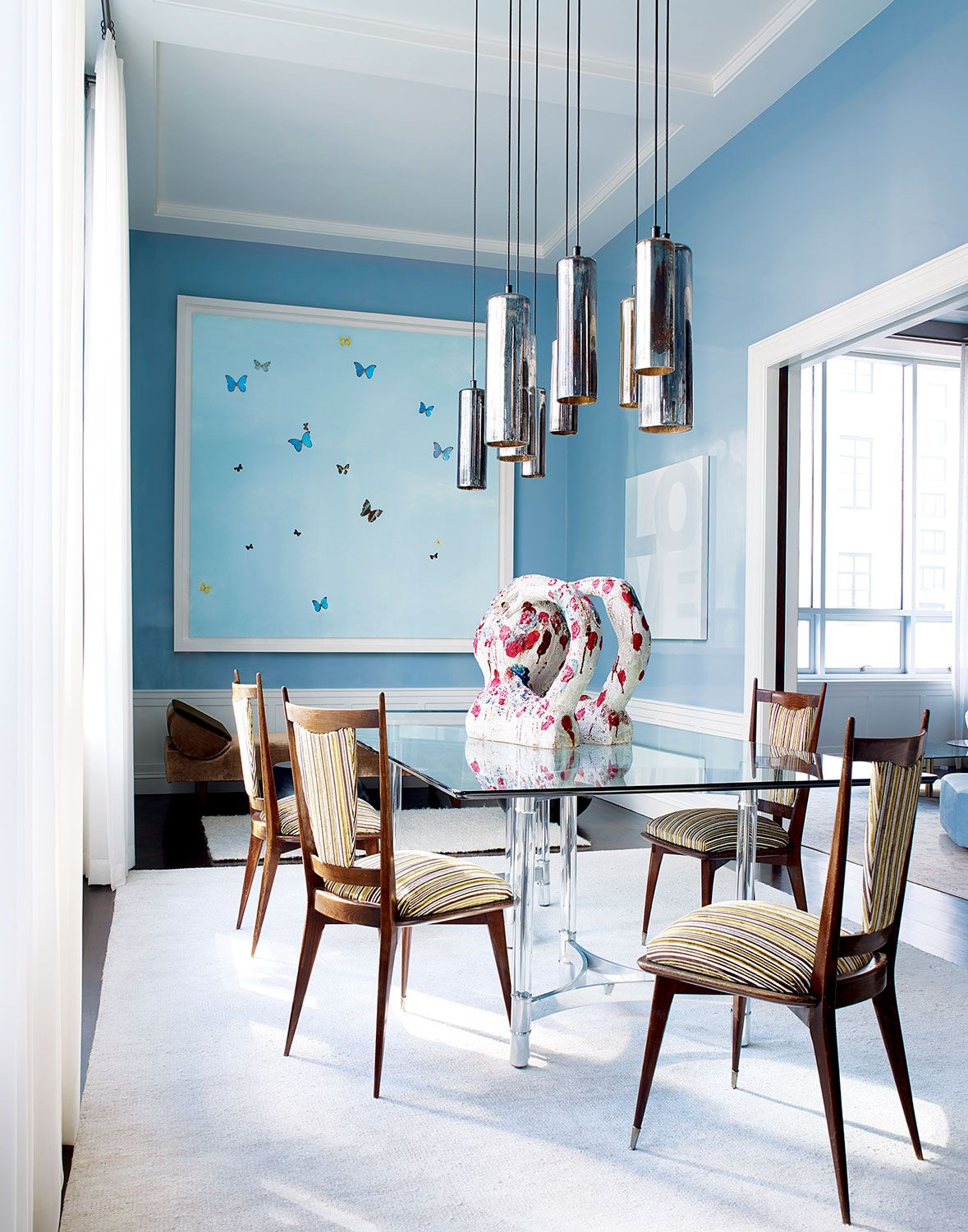 Italian chairs from the 1960s surround the vintage dining table, and the vintage mercury-glass canister pendants are by Gregory Rogan; the sculpture is by William J. O'Brien; a butterfly painting by Damien Hirst hangs above a Kevin Walz daybed by Ralph Pucci.