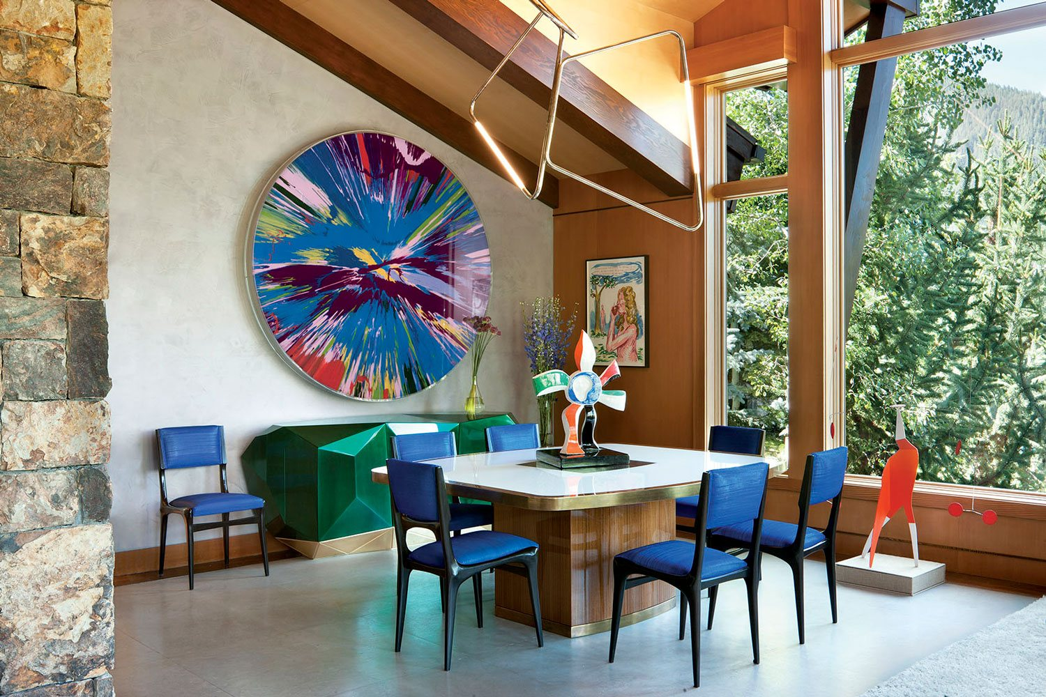 A Damien Hirst spin painting in the dining area of Sue Hostetler's Aspen home designed by Sara Story.