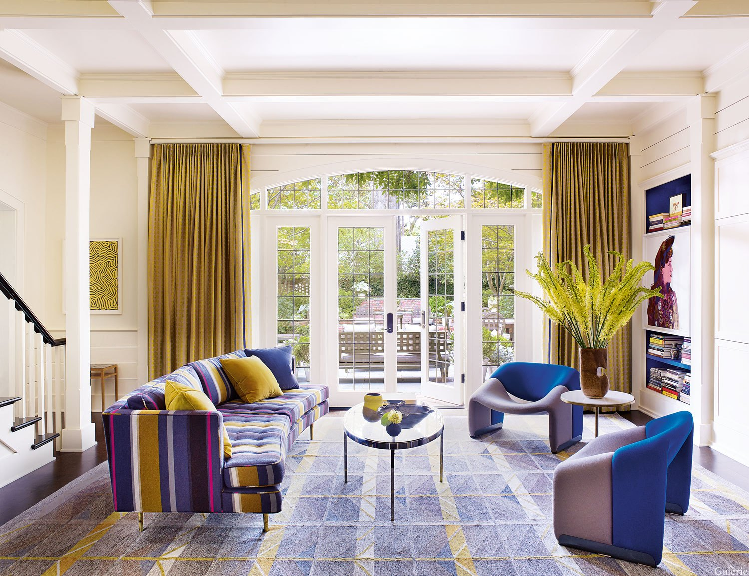 The den in the home of Dr. John and Dee Ledbetter. The 1950s Edward Wormley sofa is covered in a Knoll stripe, the chairs are vintage Pierre Paulin, and the silkscreen is by Warhol.