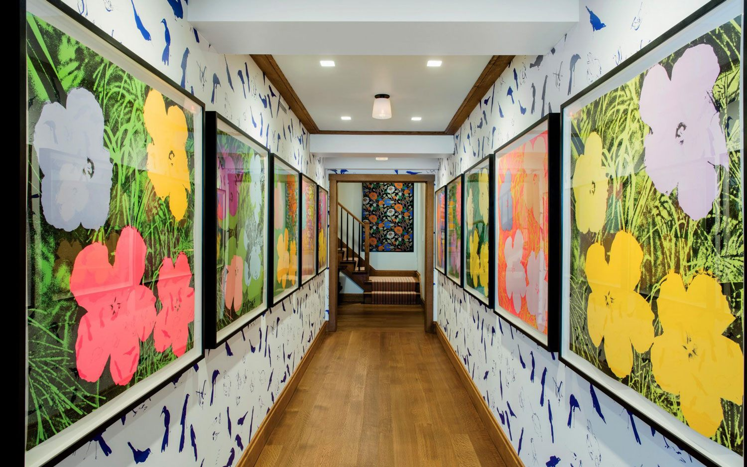 """In Jay Johnson's and Tom Cashin's home, """"Flowers,"""" a suite of ten Andy Warhol screen prints from 1970, hang in a hallway against a Billy Sullivan wallpaper custom printed by Studio Printworks."""