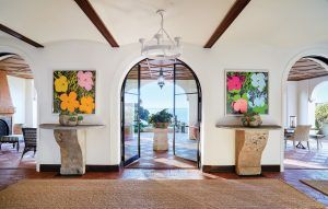 """In an airy gallery with views of the Pacific, designer Madeline Stuart installed a custom-made Paul Ferrante chandelier above Andy Warhol """"Flowers"""" paintings, 18th-century Italian stone consoles, and rugs made of woven palm matting."""