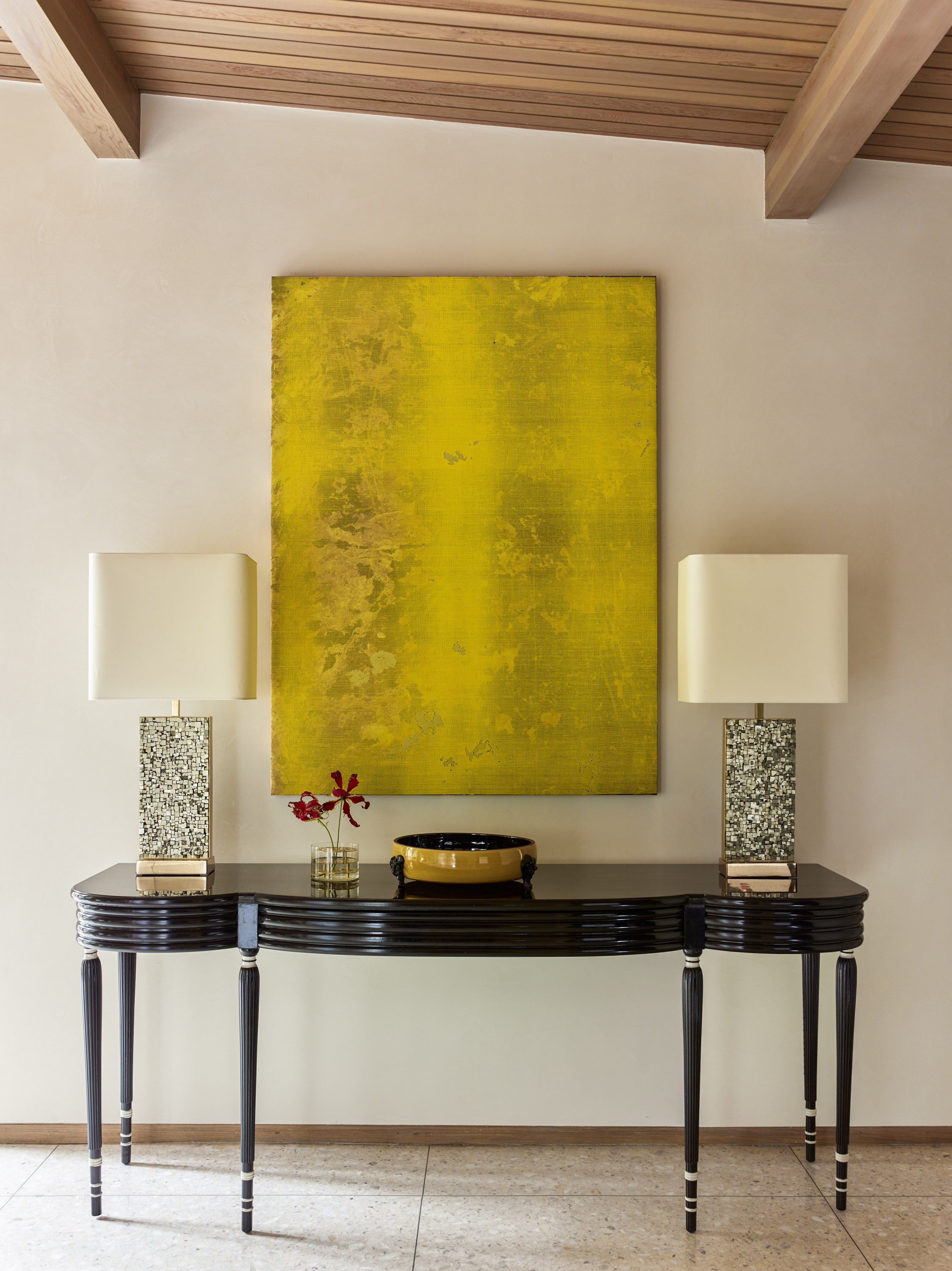 In the entryway, a console Jean Dunand is paired with brass-and-pyrite lamps by Georges Mathias and an Evan Nesbit artwork.