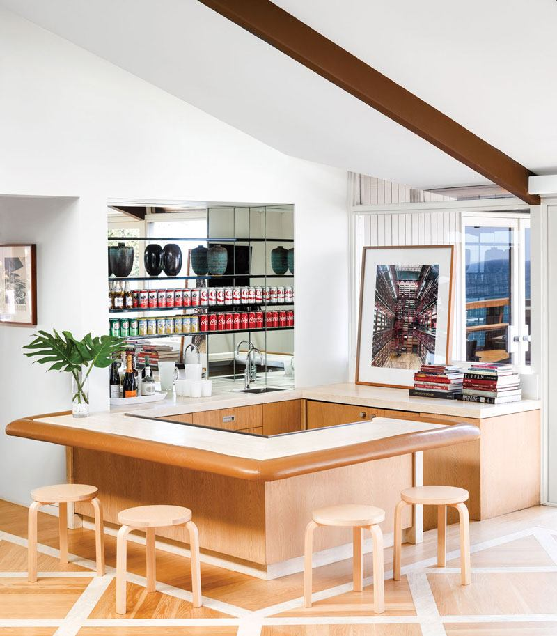 A Candida Höfer photograph is displayed in this Eddie Lee–designed residence's sunken bar, which is topped with travertine and leather; the stools are by Alvar Aalto.