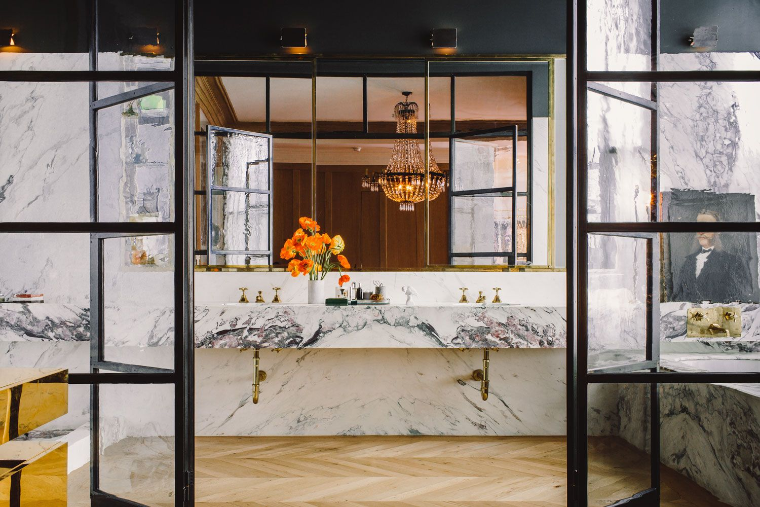 Meyer Davis Studio designed the master bath of a 19th-century cast-iron building with purple-veined Calacatta Paonazzo marble contrasting an unvarnished chevron wood floor.