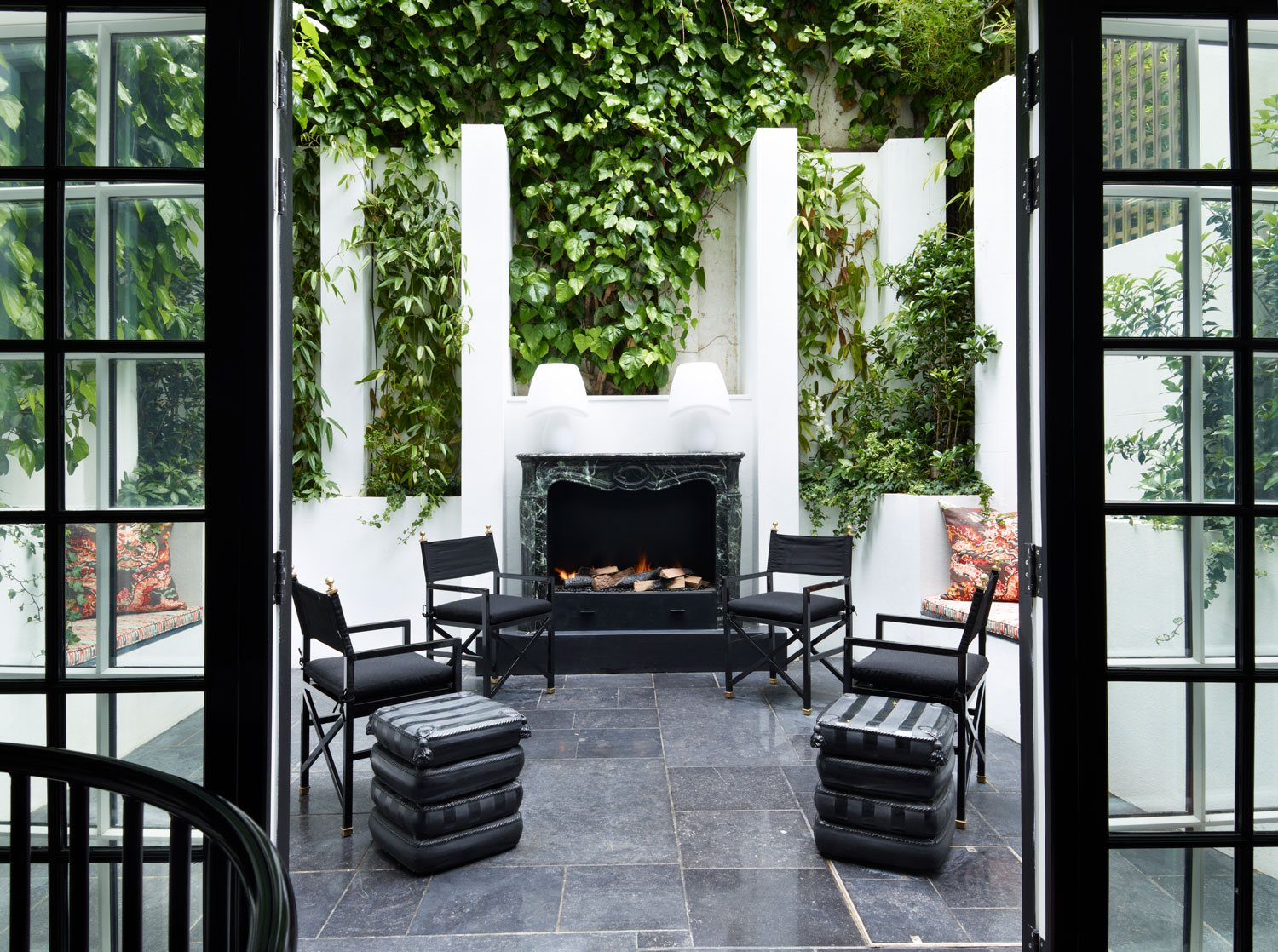This walled terrace designed by Philip Vergeylen for Nicholas Haslam Ltd. blurs the line between indoors and outdoors. The fireplace is Maurin Green marble, and the floor is reclaimed 18th-century Belgian bluestone.