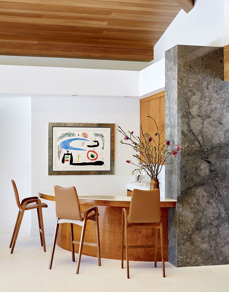 Amid wooden furnishings and a neutral color scheme, a Joan Miró is the artful statement in the home bar of Ralph and Rita Rudin.