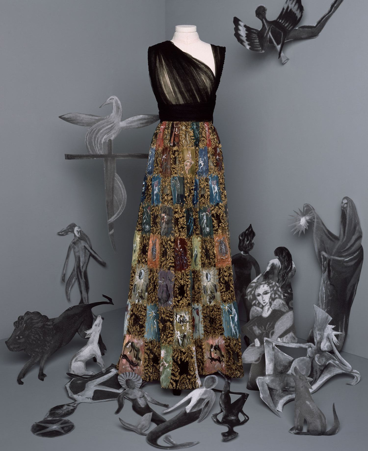 """Dior's Esphyr Look: Long black tulle dress. Asymmetrical draped bodice and skirt embroidered with a multicolored chiffon checkerboard painted with a Leonora Carrington """"Tarot"""" motif highlighted with gold thread."""